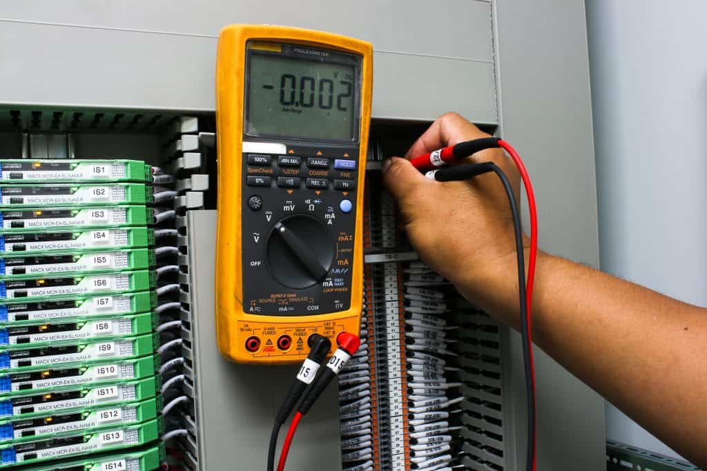 voltage meter being used on an industrial fuse board