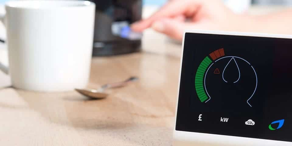 smart meter with a boiling kettle in the background along with a white cup and spoon